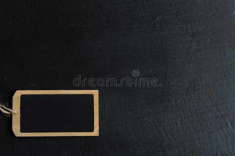 Tom svart tavlaetikett för ett kort meddelande på svart bakgrund, copyspace för din text arkivbilder