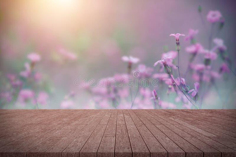 Tom tabell för träbräde framme av blommor arkivfoton