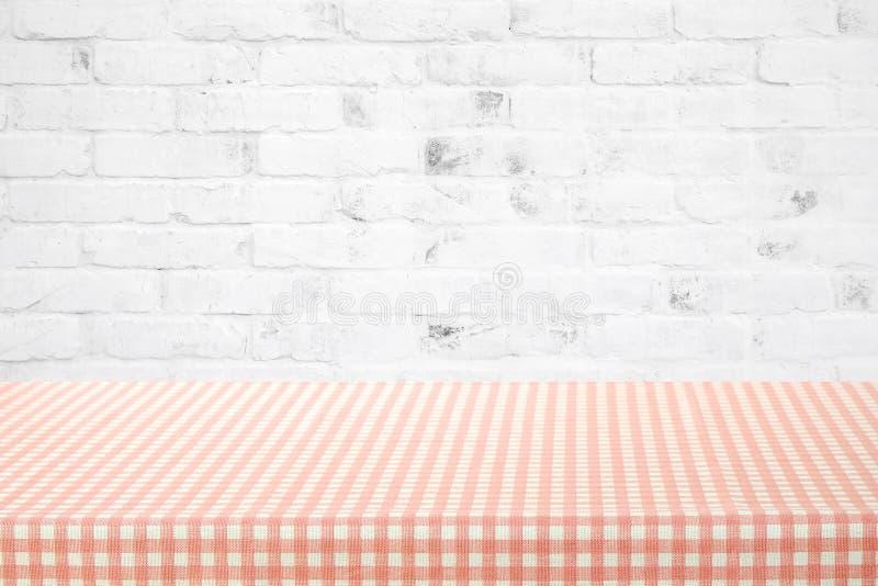 Tom tabellräkning med den rosa och vita bordduken över vitt bric arkivfoto