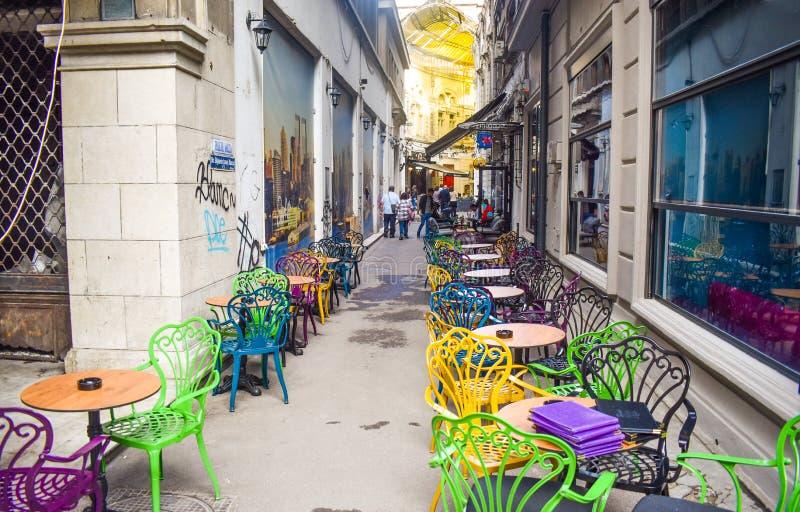 Tom tappningterrass i historiskt centrum med mång--färgade stolar på trottoartrottoaren Färgrika stolar i retro royaltyfri bild