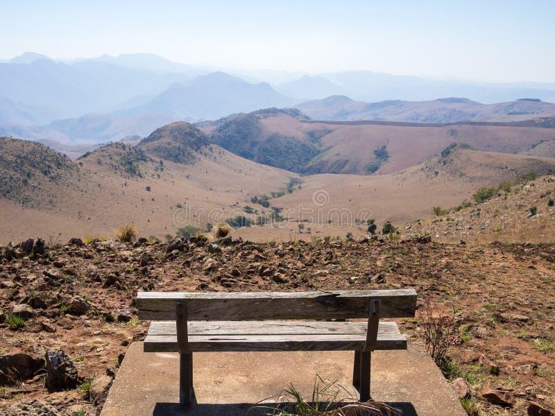 Tom träbänk som förbiser berg och ointressant landskap av den Malolotja naturreserven, Swaziland, sydliga Afrika arkivbild