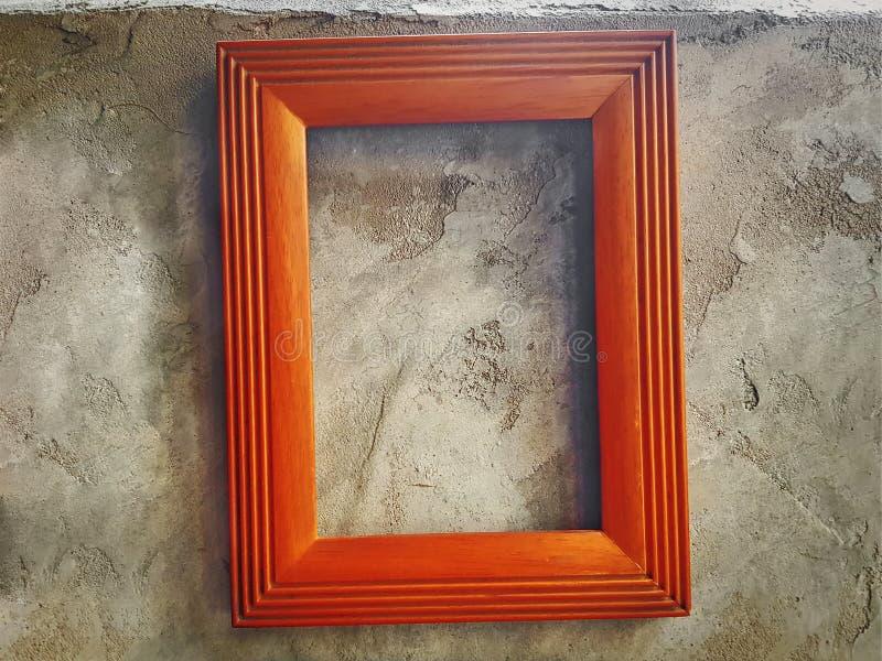 Tom träbildram som hänger på den kala Grungy cementväggen royaltyfria bilder