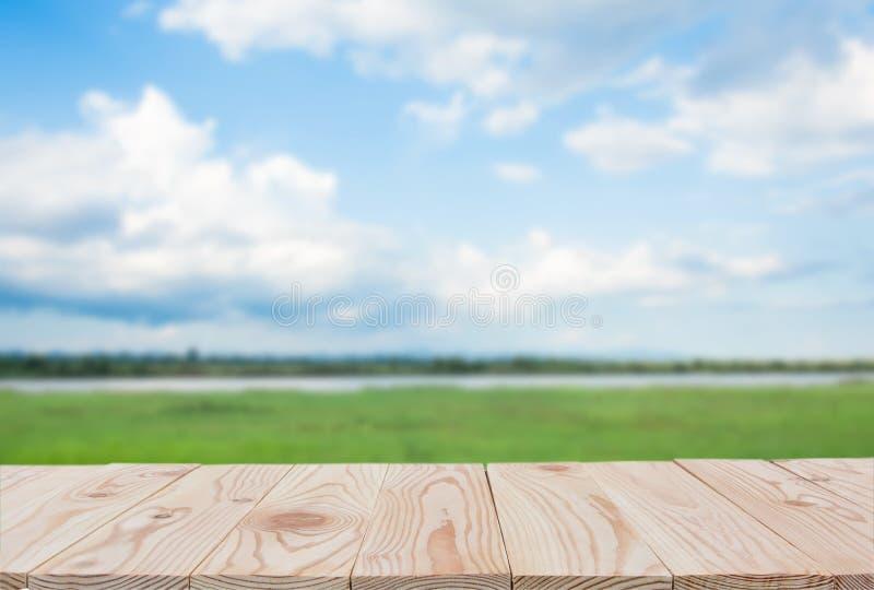 Tom träbrädetabellöverkant på av suddig blå himmel- och flodbakgrund med kopieringsutrymme för skärm eller montage dina produkter royaltyfria bilder