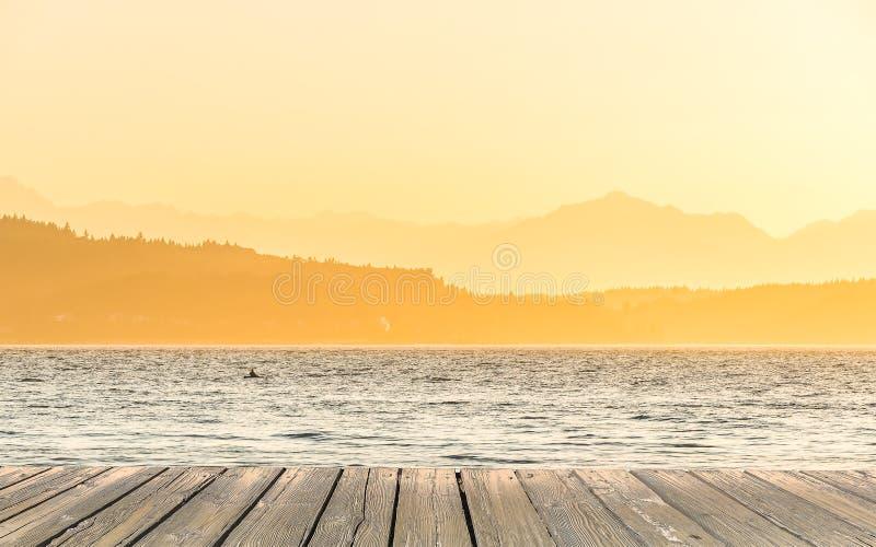 Tom trädäcktabellöverkant som är klar för produktskärmmontage med havet när solnedgångbakgrund arkivfoto
