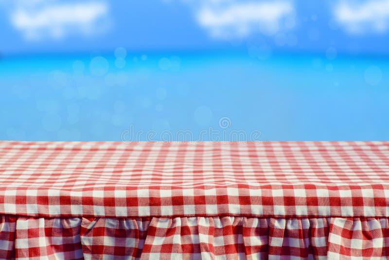Tom trädäcktabell med den röda rutiga bordduken över abstr royaltyfria bilder