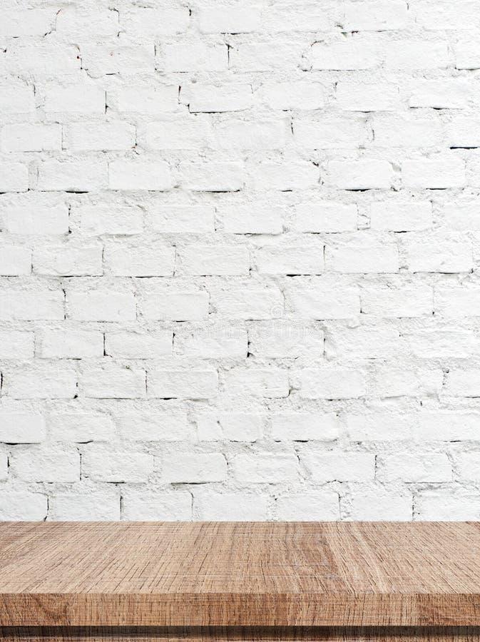Tom trätabell över vit bakgrund för tegelstenvägg royaltyfria foton