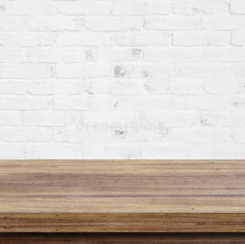 Tom trätabell över vit bakgrund för tegelstenvägg, för produc arkivfoton