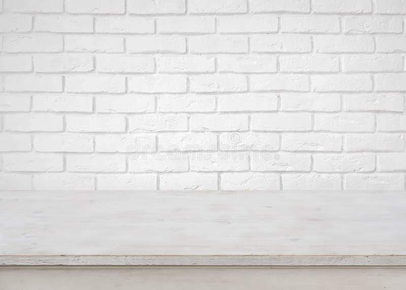 Tom trätabell för tappning på defocused vit bakgrund för tegelstenvägg arkivfoton