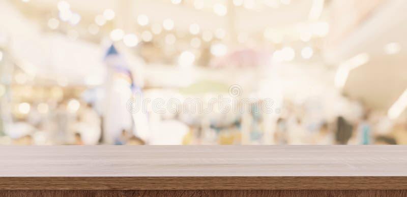 Tom trätabell och suddig ljus tabell i shoppinggalleria med bokehbakgrund produktsk?rmmall arkivfoto
