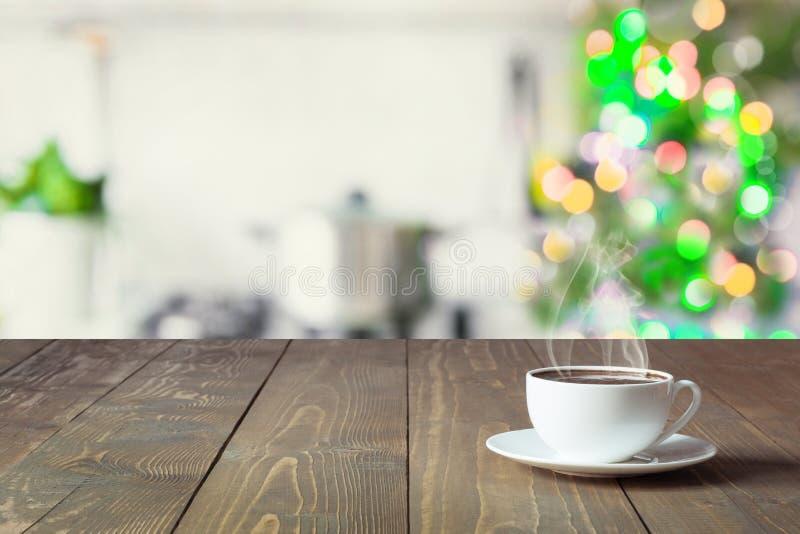 Tom trätabletop för skärmprodukter och suddigt kök med julgranen som bakgrund arkivbild