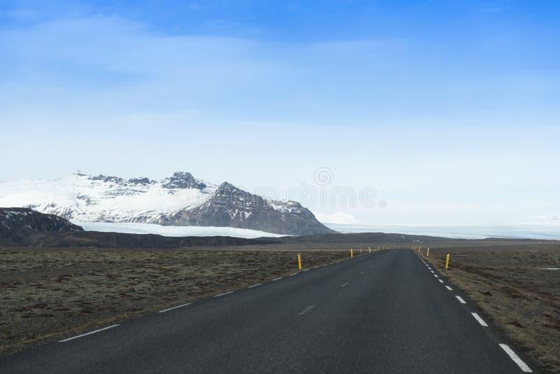 Tom väg som leder för att snöa dolda berg, härlig landscap arkivbilder