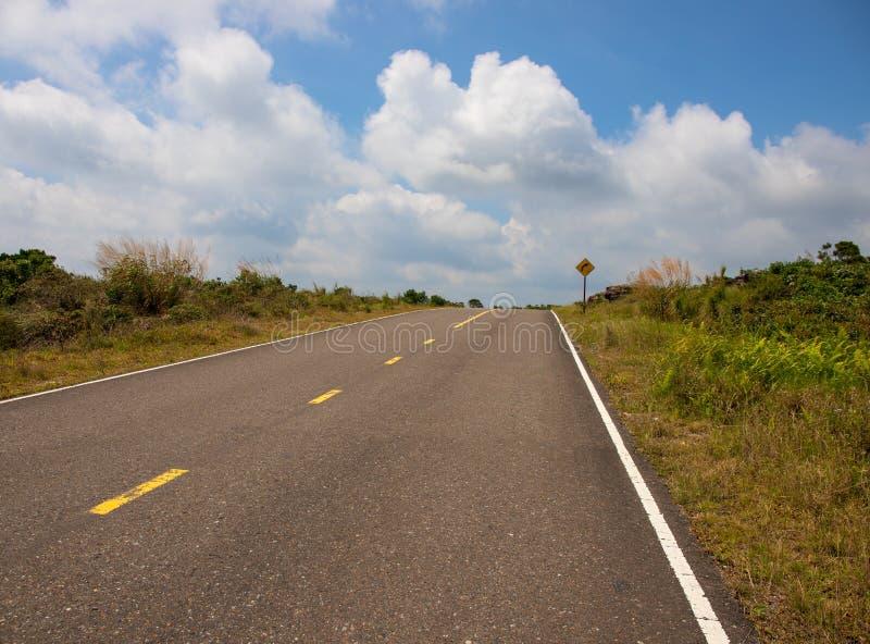 Tom väg till molnig himmel Rak väg i gröna kullar Tropisk vägren Vänd det höger tecknet royaltyfria bilder