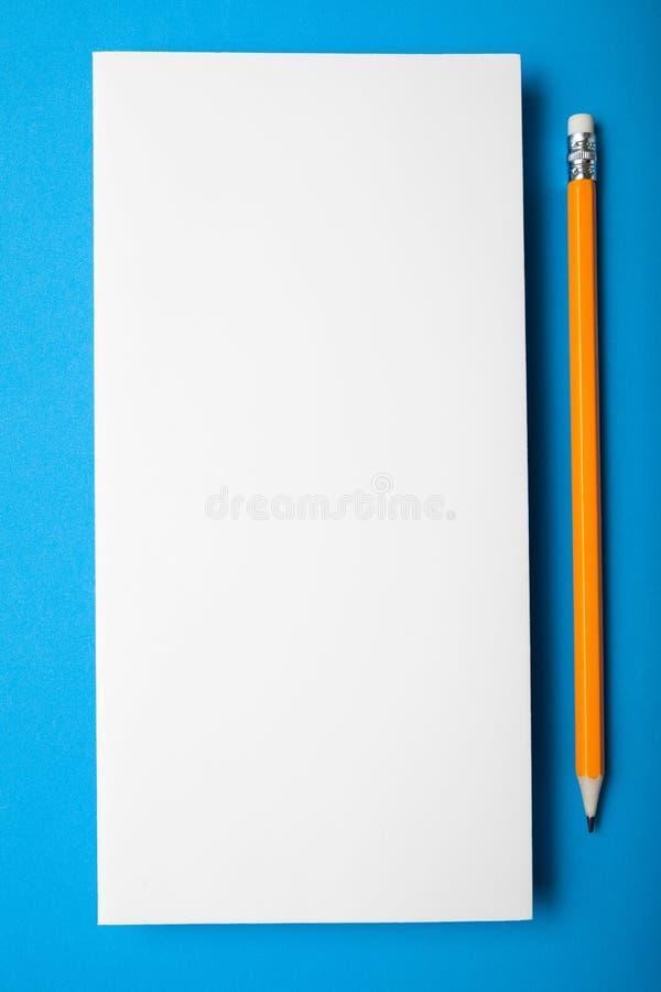 Tom vertikal vykort eller inbjudan på en blå bakgrund arkivfoton