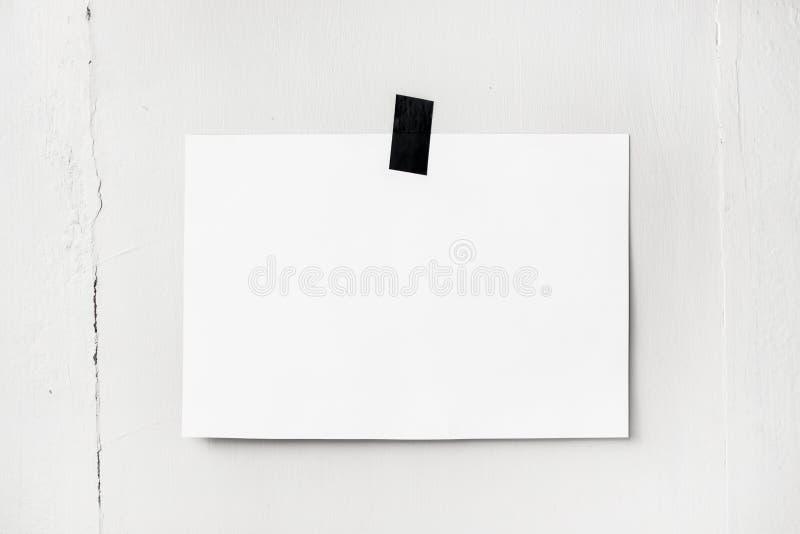 Tom vit affisch som hänger på ett band på väggen Mallbackg fotografering för bildbyråer