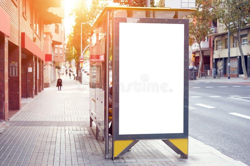 Tom vit annonserande stads- affischtavla nära stadshållplatsen, placeholdermall på en gata, utrymme för designorientering Solnedg fotografering för bildbyråer