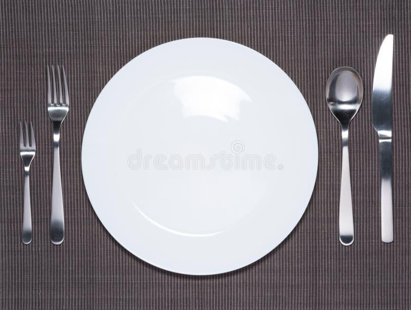Tom vit maträtt, gaffel, sked och kniv arkivbild