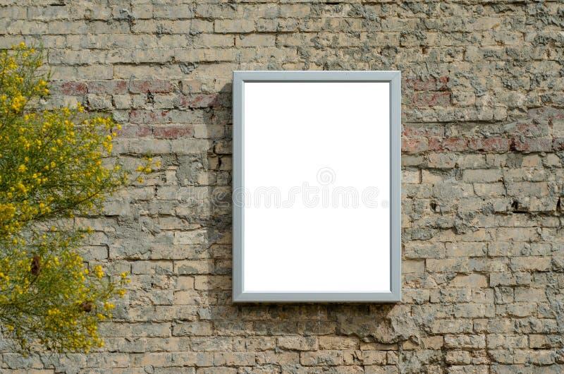 Tom vit modell upp-mall för affisch med stålram på gammal tegelvägg fotografering för bildbyråer