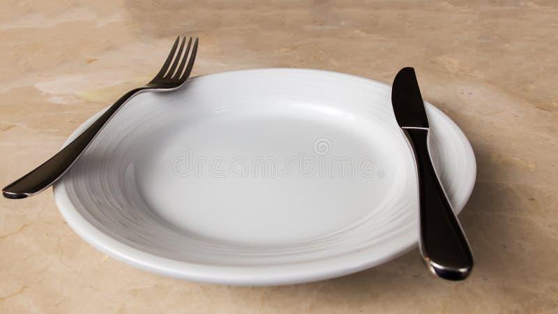 Tom vit platta med gaffeln och kniv på marmorstentabellen royaltyfria bilder