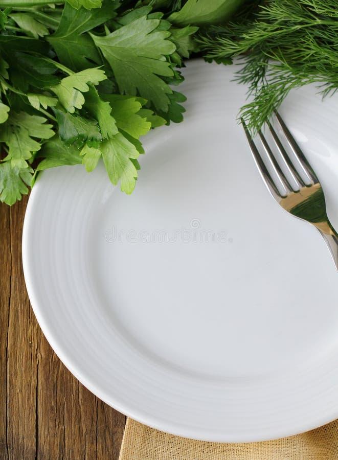 Tom vit platta med gaffeln på trätabellen royaltyfri foto
