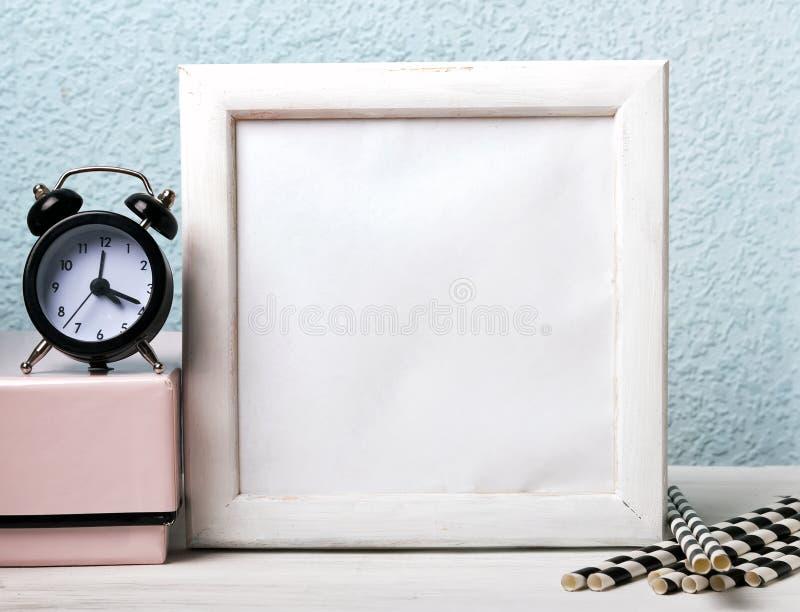 Tom vit ram, svart klocka och pappers- sugrör royaltyfri fotografi