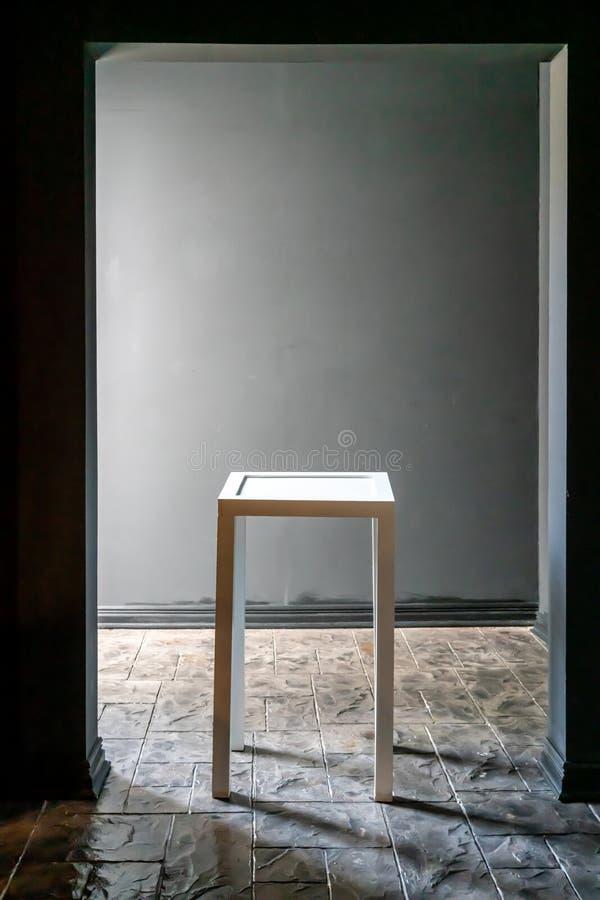Tom vit tabell på stengolv mot mörk grå bakgrund royaltyfri foto