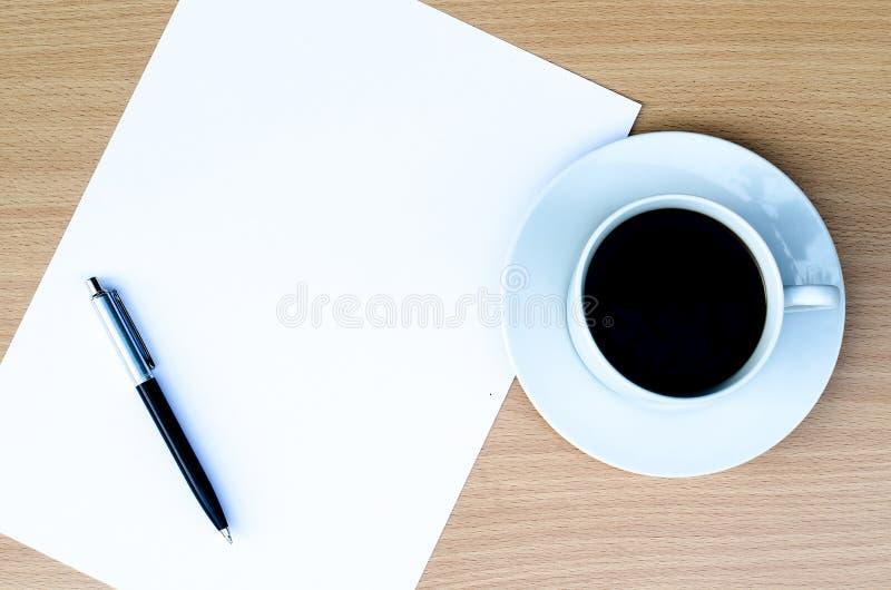 Tom vitbok är på tabellen med bollpennan och kaffe åt sidan arkivbild