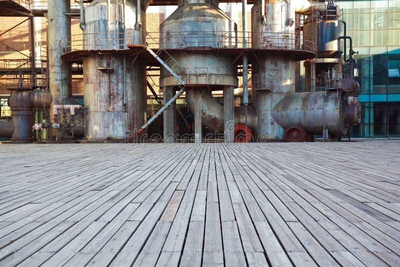 Tom wood golvvägyttersida med gammal stålstålverk av rörledningar arkivbilder