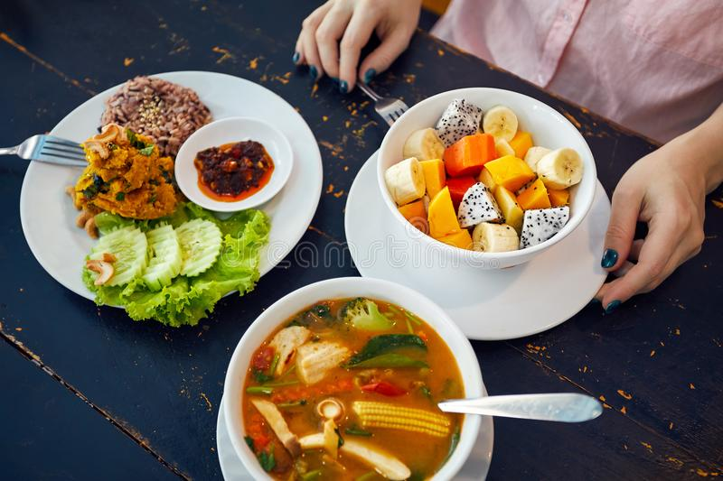 Tom yam, curry and fruit salad. Thai traditional sour soup Tom Yam in vegetarian variation, curry rice and t salad in vegan restaurant in Bangkok royalty free stock image