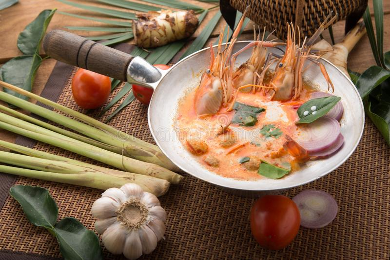 Tom yam kong or Tom yum, Tom yam is a spicy clear soup typical in Thailand Cuisine. Tom yam kong on wooden table. Thai food stock images