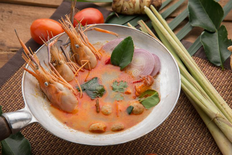 Tom yam kong or Tom yum, Tom yam is a spicy clear soup typical in Thailand Cuisine. Tom yam kong on wooden table. Thai food royalty free stock photography