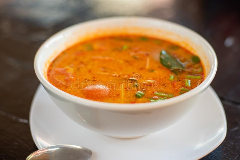 Tom Yam kung Spicy Thai soup with shrimp, seafood, coconut milk and chili pepper in bowl copy space stock photo