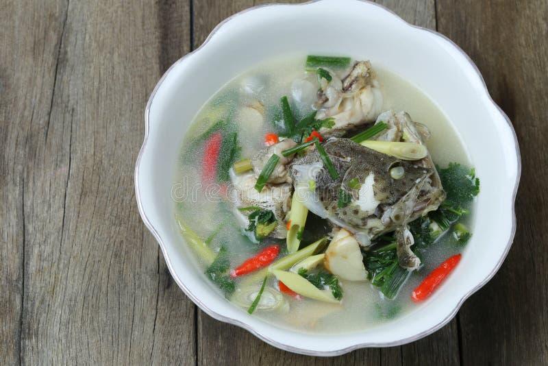 Tom Yum Grouper Fish Spicy Soup de la comida tailandesa en un cuenco en piso de madera imagenes de archivo