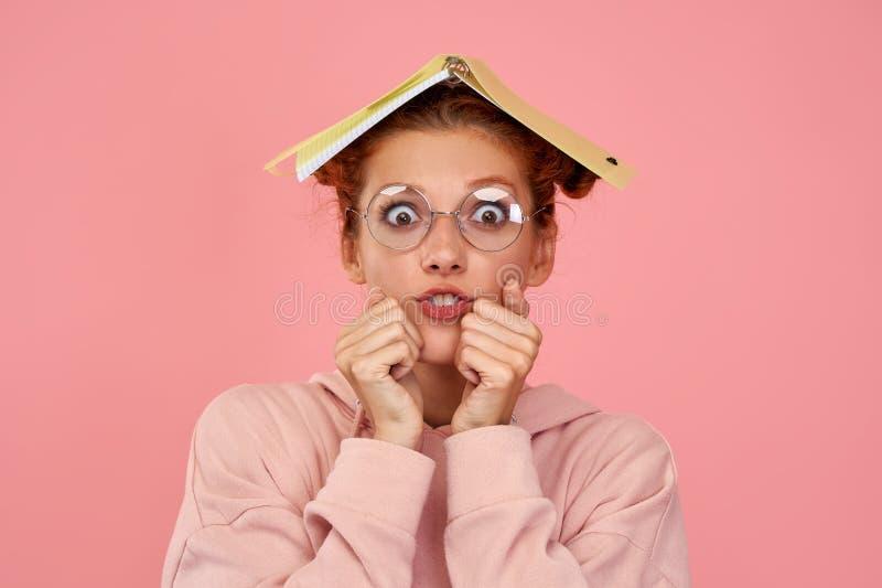 Toma horizontal de las ansiosas uñas mordidas de jengibre por perplejidad, tiene libro de texto en la cabeza, se ve estresante fotografía de archivo