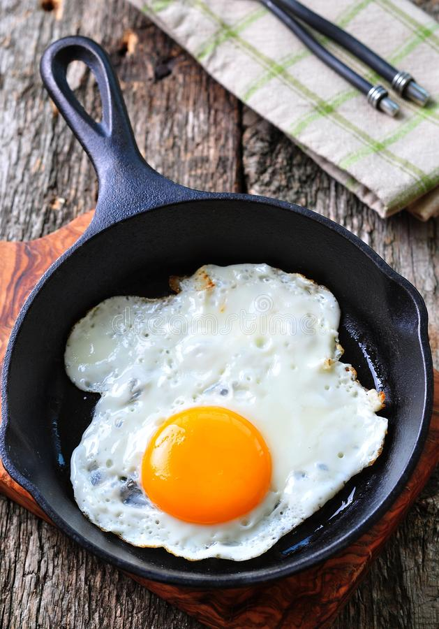 Toma o café da manhã o ovo frito em uma frigideira do ferro foto de stock