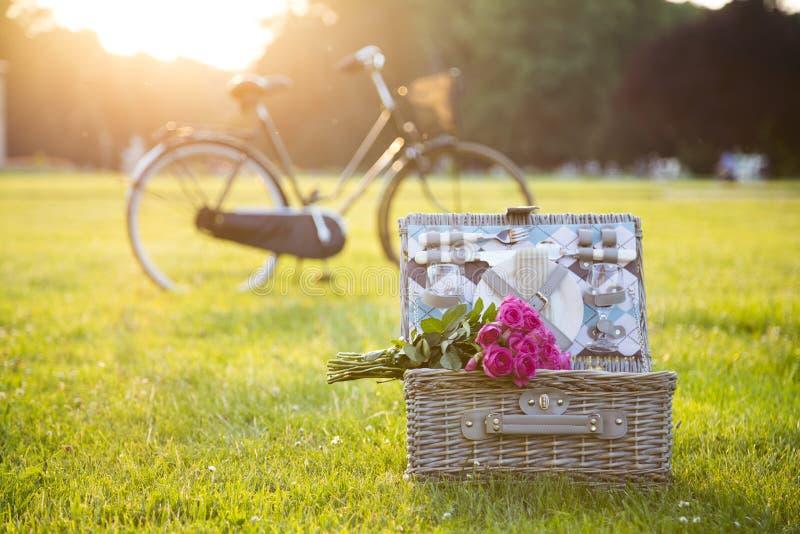 Toma parte num piquenique a cesta, ramalhete, bicicleta na grama no parque imagens de stock