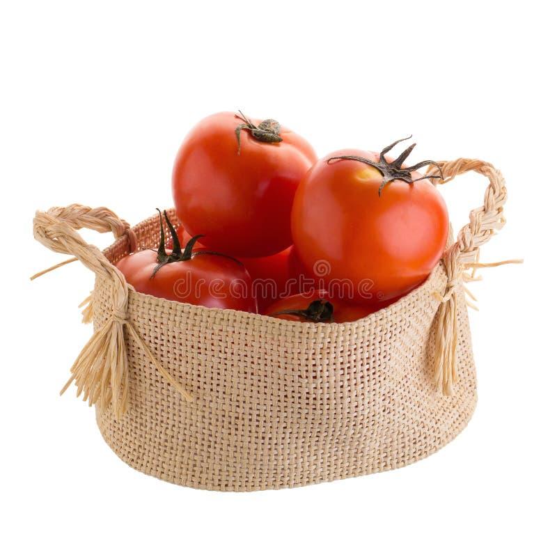 Tomaat in de mand op een witte achtergrond wordt geïsoleerd die stock fotografie