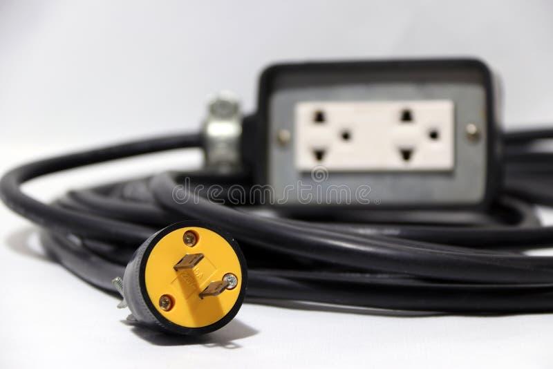 A tomada amarela e centra-se para fora a tomada com cabo preto sobre o fundo branco Usado para a conexão elétrica imagem de stock royalty free