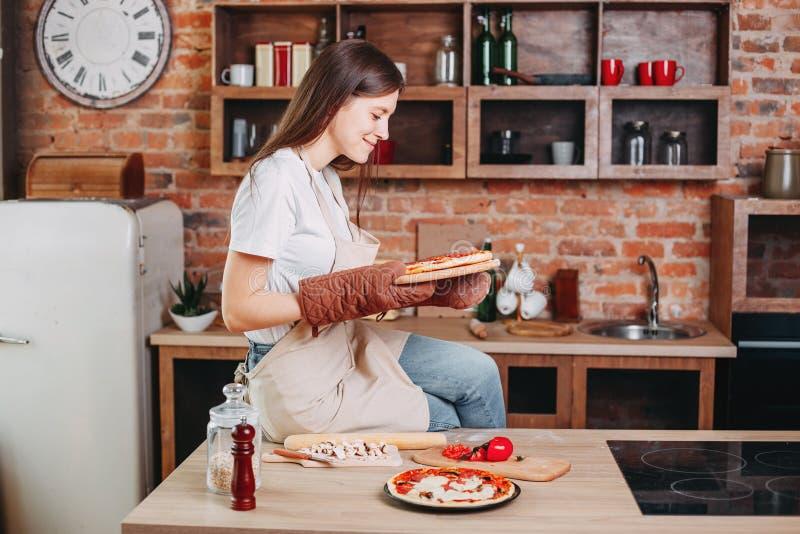 Tomada da dona de casa da mulher que admira o olhar na pizza cozida imagem de stock royalty free