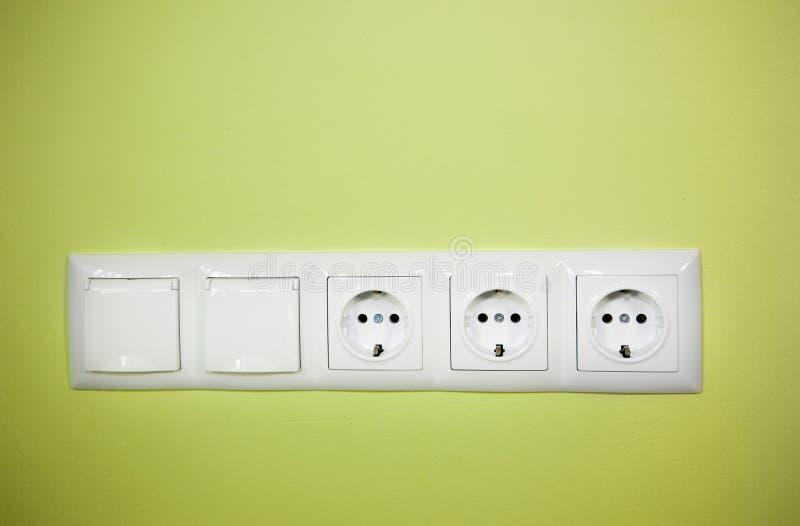 Tomada de parede elétrica/no fundo verde imagem de stock