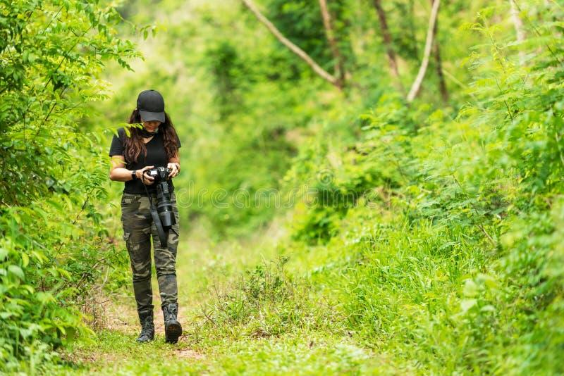 Tomada do fot?grafo da mulher profissional exterior com a lente principal na natureza verde da floresta tropical da selva imagens de stock