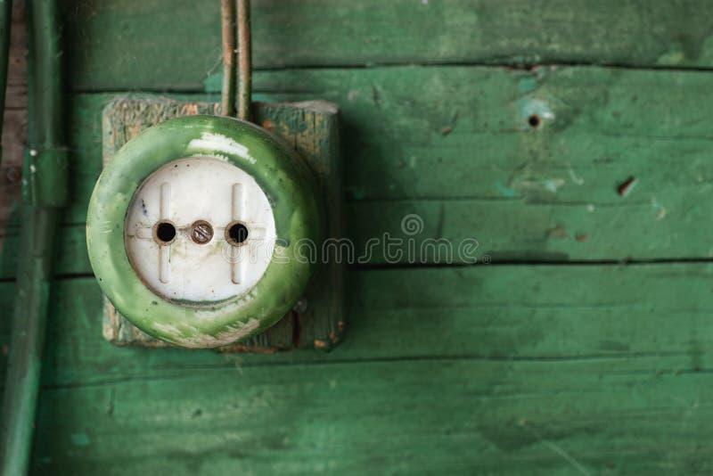 Tomada elétrica velha na parede de madeira verde imagem de stock