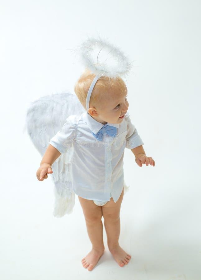 Tomada em uma atmosfera do feriado Anjo do bebê Menino pequeno adorável do anjo Rapaz pequeno com asas e halo do anjo cute fotos de stock royalty free