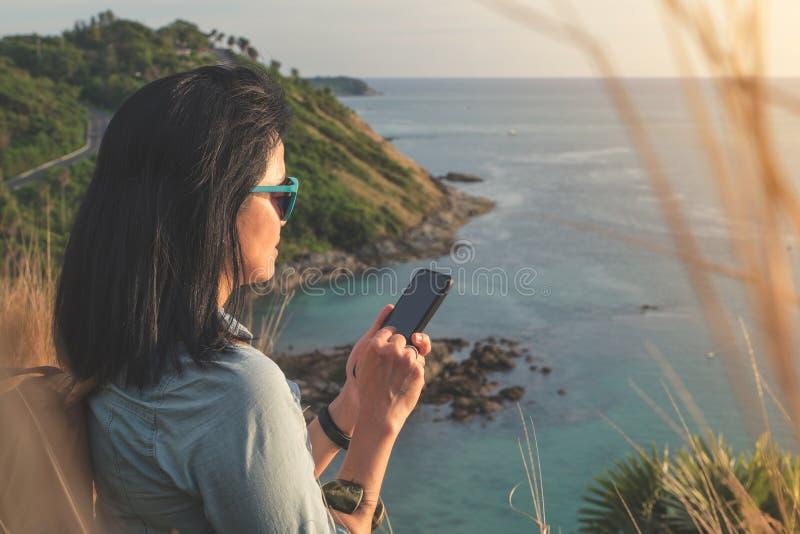 Tomada nova do telefone celular do uso da mulher do viajante da foto no beautif foto de stock