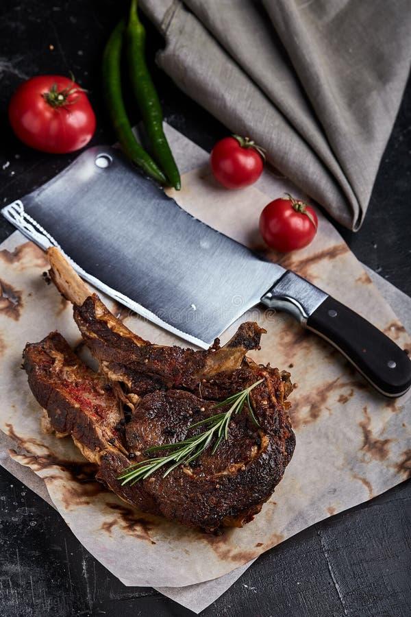 Tomahawkbiff med grönsaker och en kniv på tabellen Grillat kött med grillade grönsaker och nya grönsaker på fotografering för bildbyråer