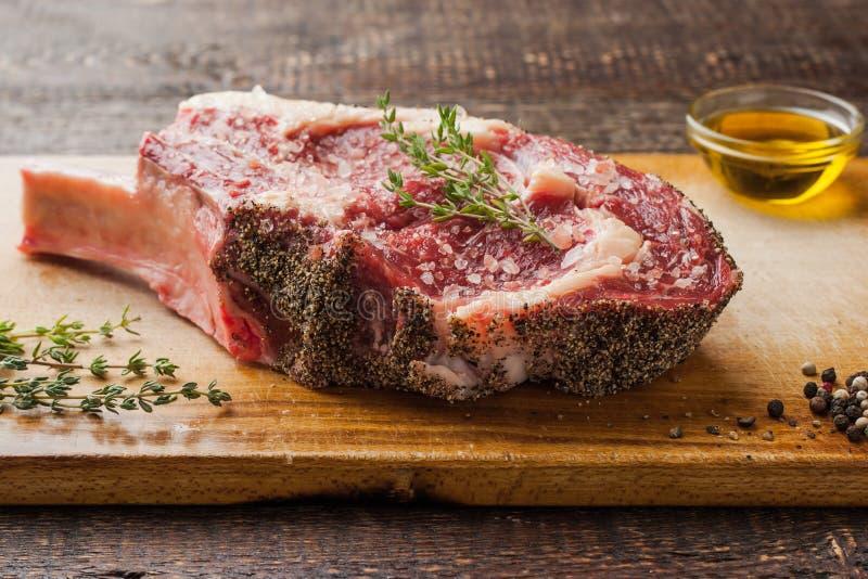Tomahawklapje vlees op het been met thyme op scherpe raad stock afbeelding