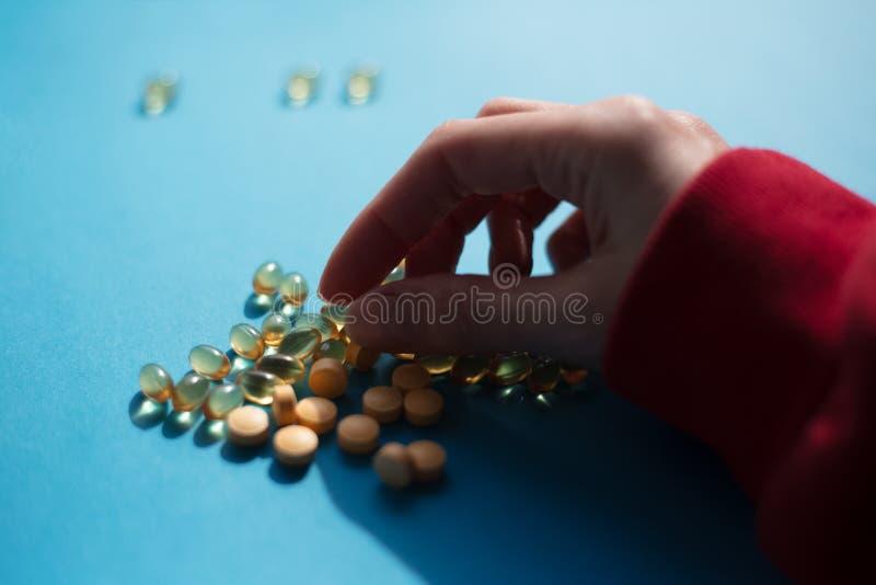 Tomando comprimidos da medicina da vitamina sobre o fundo azul fotos de stock royalty free