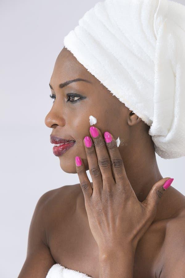 Tomando de sua pele Retrato da mulher afro-americana nova bonita envolvida no creme de espalhamento de toalha em sua cara imagens de stock royalty free
