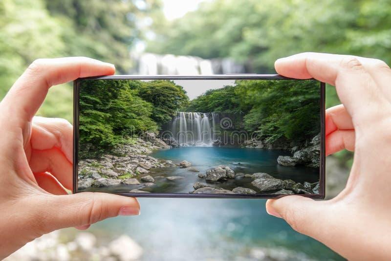 Tomando a foto da cachoeira de Cheonjeyeon na ilha de Jeju, Coreia do Sul com telefone celular Turismo ativo em Ásia foto de stock