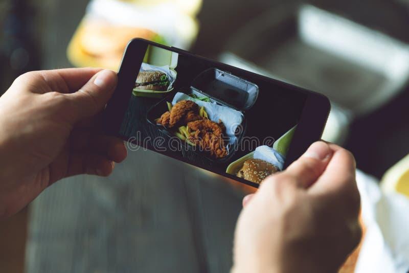 Tomando a foto do Hamburger, das batatas fritas e do frango frito em uns recipientes afastados com telefone esperto Entrega do al imagem de stock royalty free