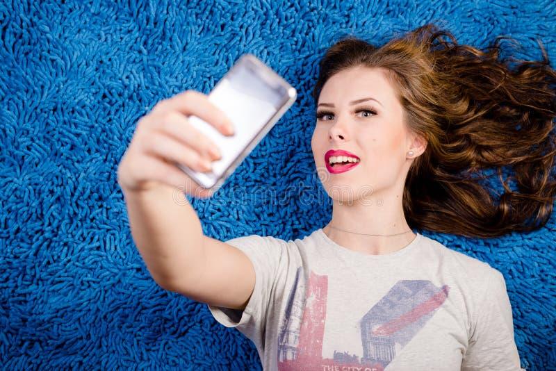 Tomando a imagem do auto a mulher bonita nova 'sexy' que relaxa sobre a cópia azul espace o tapete fotografia de stock royalty free